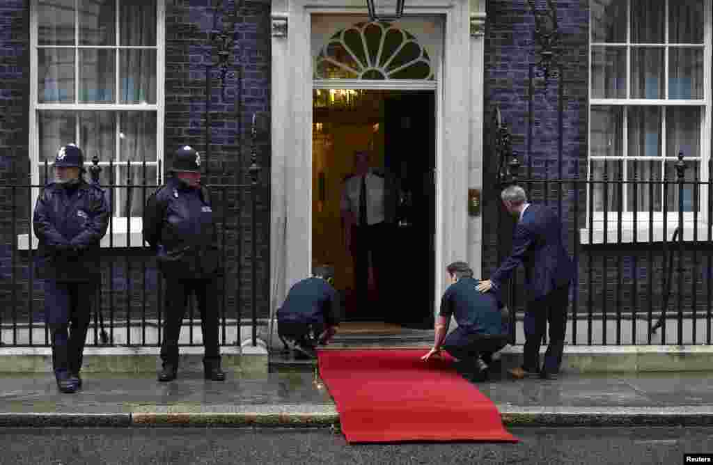 Workers place a red carpet ahead of a meeting between Prime Minister David Cameron and President Xi Jinping at 10 Downing Street, in central London, Oct. 21, 2015.
