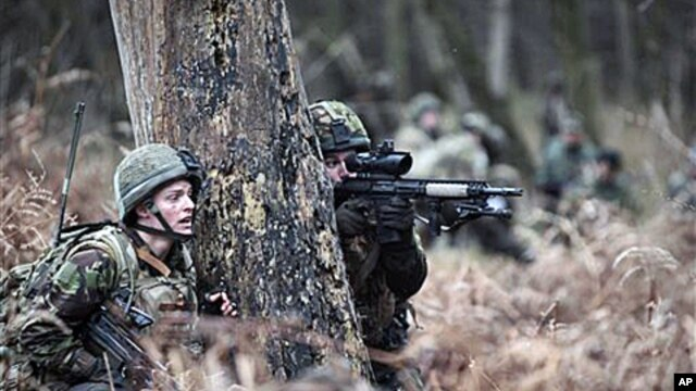 British soldiers from 1 Rifles, return 'fire' as they are 'ambushed' during a training session prior to deployment, at British forces' Stanford Training Area in Norfolk, England, 14 Jan 2011