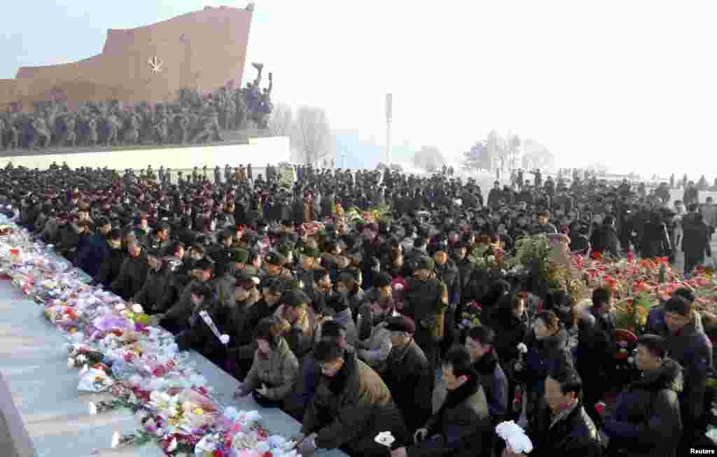 Warga Korea Utara menyimpan bunga di depan patung-patung Kim Il Sung dan Kim Jong Il di bukit Mansudae di Pyongyang, pada acara peringatan dua tahun kematian Kim Jong Il (17/12). (KCNA)