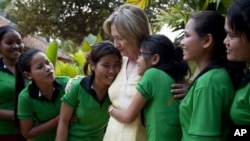 A group of girls reach in to hug U.S. Secretary of State Hillary Rodham Clinton during a tour of the Siem Reap Center, a shelter run by AFSEIP that provides rehabilitation, vocational training, and social reintegration for sex trafficking victims, on Sund