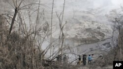 Жители деревни Гамбер наблюдают за последствиями извержения вулкана Синабург. Индонезия. 22 мая 2016 г.