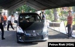 Kendaraan yang masuk halaman Gedung Negara Grahadi, Surabaya, Jawa Timur, harus melewati tenda penyemprotan disinfektan. (Foto: VOA/Petrus Riski)