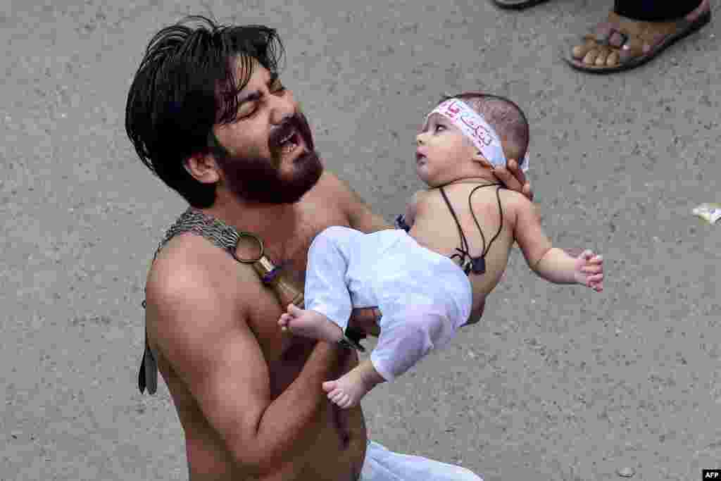 A Shi'ite Muslim holds his son before starting flagellating himself for an Ashura procession during the month of Muharram in Lahore, Pakistan.