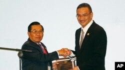 现任轮值主席国马来西亚的防长希山慕丁·侯赛因(Hishamuddin Hussein,右)向老挝国防部部长任桑努·沙雅拉(Sengnouane Sayalat)做了东盟轮值主席国转交。