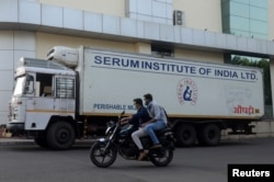 Men ride on a motorbike past a supply truck of India's Serum Institute, the world's largest maker of vaccines, which is working on a vaccine against the coronavirus disease (COVID-19) in Pune, India, May 18, 2020