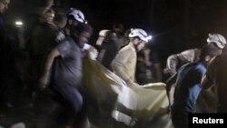 Các thành viên dân phòng khiêng một nạn nhân ra khỏi hiện trường sau vụ không kích bệnh viện tại thị trấn al-Sukari Aleppo, Syria, ngày 27/4/2015.