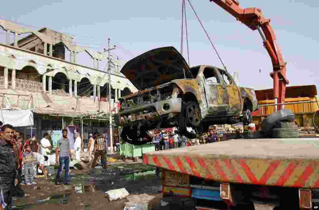 A wrecked truck is removed from the site of a car bomb attack in front of a crowded popular restaurant in Basra, Iraq, May 20, 2013.