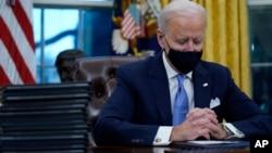លោកប្រធានាធិបតី Joe Biden ផ្អាកបន្តិច នៅពេលលោកចុះហត្ថលេខាលើបទបញ្ជាប្រធានាធិបតីដំបូងៗរបស់លោកនៅក្នុងការិយាល័យប្រធានាធិបតីក្នុងសេតវិមាន កាលពីថ្ងៃពុធ ទី២០ ខែមករា ឆ្នាំ២០២១ នៅរដ្ឋធានីវ៉ាស៊ីនតោន។