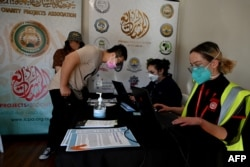 Health workers register residents for their first doses of the AstraZeneca vaccine at a COVID-19 vaccination center in the Bankstown suburb of Sydney, Aug. 7, 2021, as Australia's state of New South Wales reported another record day of infections.