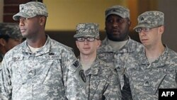 Binh nhất Bradley Manning (giữa) được đưa ra khỏi tòa án ở Fort Meade, bang Maryland
