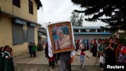 FILE - A Tibetan man carries a portrait of Dalai Lama during a function organized to mark the 82nd birthday celebration of Dalai Lama in Lalitpur, Nepal, July 6, 2017.