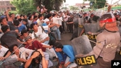 Indonesian students fall as riot policemen charge-in during an anti-government demonstration that turned violent at the gate of the Sahid University in Jakarta 29 April, 1998. Clashes erupted as some 300 students who were demanding President Suharto to s