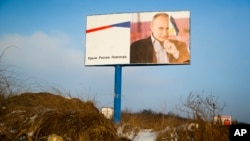 "FILE - A partially damaged billboard featuring a picture of Russian President Vladimir Putin is seen on a roadside near Simferopol, Crimea, Jan. 24, 2016. The billboard reads: ""Crimea. Russia. Forever."""