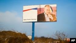 "FILE - A partially damaged billboard with a portrait of Russian President Vladimir Putin is seen on a roadside near Simferopol, Crimea, Jan. 24, 2016. The billboard reads: ""Crimea. Russia. Forever."""