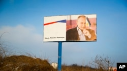 "FILE - A partially damaged billboard with a portrait of Russian President Vladimir Putin is seen on a roadside near Simferopol, Crimea, Jan. 24, 2016. The billboard reads: ""Crimea. Russia. Forever."""