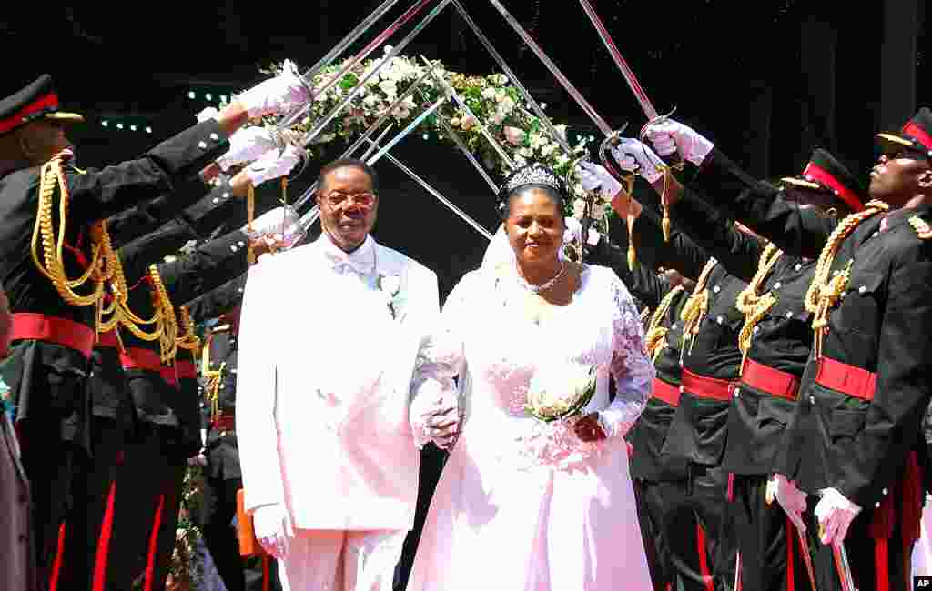 President Bingu wa Mutharika and his Bride Callista walk under a military sword salute by officers of the Malawian defense forces after their wedding ceremony at Civo stadium in Lilongwe, April 17, 2010. (AFP Photo)