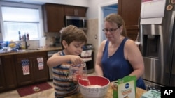 Logan Strauss, 5, adds water to a cake mix while baking with his mother Karen at their home in Basking Ridge, N.J., Wednesday, July 28, 2021. Logan will continue with remote learning from home until he can get the COVID-19 vaccination. (AP Photo/Mark Lennihan)
