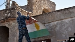An Iraqi soldier removes a Kurdish flag from Altun Kupri on the outskirts of Irbil, Iraq, Oct. 20, 2017.