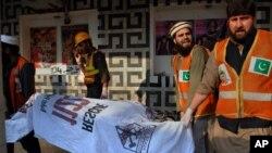 파키스탄 페샤와르 시의 한 영화관에서 11일 수류탄 공격이 발생한 가운데, 구조대원들이 사망자들을 옮기고 있다.