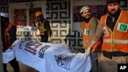 Nhân viên cứu hộ Pakistan dời các thi thể khỏi hiện trường vụ tấn công vào 1 rạp chiếu phim ở Peshawar, Pakistan, 11/2/2014