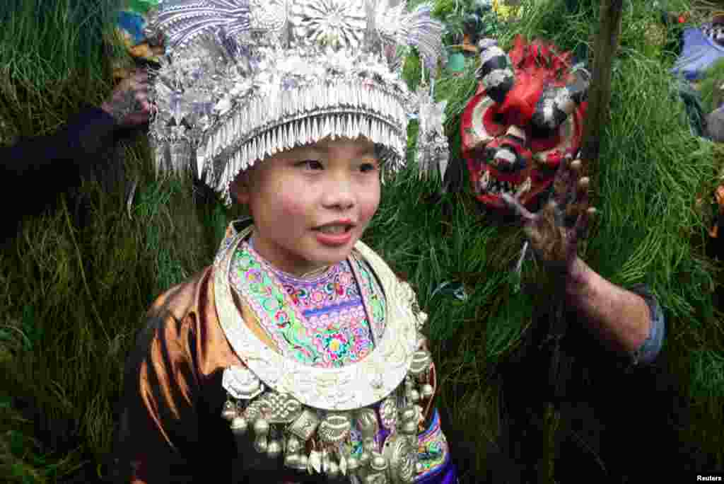 "An ethnic Miao woman poses with Miao men dressed as ""Manghao"" during an event to celebrate the Manghao Festival at Rongshui Miao Autonomous County, in Liuzhou, Guangxi Zhuang Autonomous Region, China, Feb. 13, 2019."