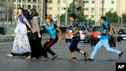 Jeunes égyptiens harcelant des femmes qui traversent la route au Caire, en Égypte, le 20 août 2012. L'un d'eux va jusqu'à la toucher sur les fesses, ce qui arrive fréquement en Egypte, sans que les autorités ne réagissent ou n'interviennent (Photo AP/Ahmed Abd el Latif)