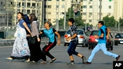 FILE - In this Aug. 20, 2012 file photo, an Egyptian youth, trailed by his friends, gropes a woman crossing the street with her friends in Cairo, Egypt. (AP Photo/Ahmed Abd El Latif, El Shorouk Newspaper, File)
