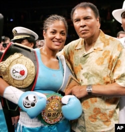 FILE - Laila Ali, left, poses with her father, boxing great Muhammad Ali, after her win against Erin Toughill at the MCI Center in Washington, June 11, 2005.