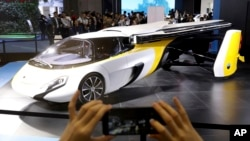 A visitor takes a photo of the Aeromobil, a flying car from Slovakia, during the China International Import Expo in Shanghai, Nov. 5, 2018.