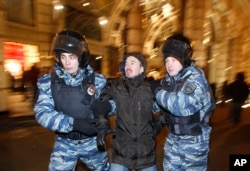 FILE - Police detain a man during an unsanctioned protest in Moscow, Russia, Dec. 30, 2014.
