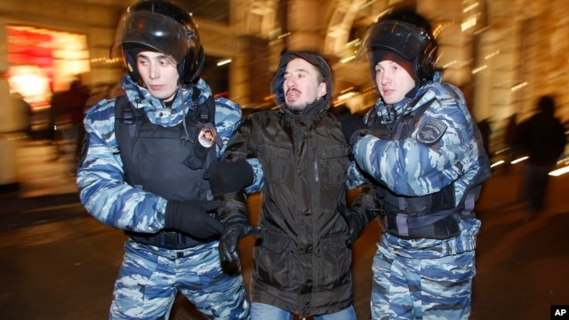 FILE - Police officers detain a protester during an unsanctioned protest in Moscow, Russia, Dec. 30, 2014.