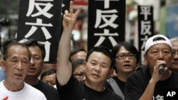 FILE - Xiong Yan flashes a victory sign during a march in Hong Kong marking the 20th anniversary of the military crackdown on a pro-democracy student movement in Beijing, May 31, 2009.