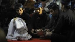 "Suku Baduy berdoa di depan seikat padi yang baru dipanen saat upacara di istana Cigugur Pangeran Djati Kesuma, dihiasi dengan buah-buahan yang baru dipanen dalam upacara panen tahunan tradisional selama seminggu yang dikenal sebagai ""Seren Taun"" di Cigugu"