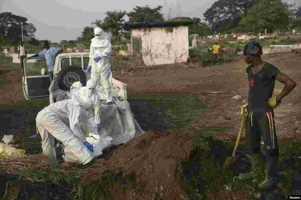 Un fossoyeur attend pelle en main pour enterrer le corps d'une victime d'Ebola que le personnel de santé amène à un cimetière à Freetown, 17 décembre 2014. REUTERS / Baz Ratner