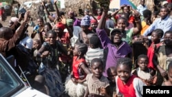 Internally displaced people celebrate during a distribution of tarps in Mubimbi, South Kivu, Democratic Republic of Congo, March 4, 2013.