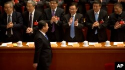 Delegates applaud as Chinese President, Xi Jinping, passes.
