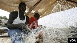 Nelayan Guinea-Bissau sedang meyiapkan jala untuk menangkap ikan. Mereka kalah bersaing dengan nelayan-nelayan Uni Eropa yang mempunyai peralatan lebih moderen.