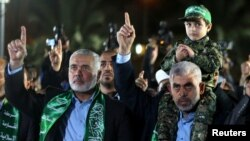 Ismaïl Haniyeh, le chef du Hamas, salue la main levée, lors de sa visite à Gaza, à côté de Yahya Al-Sinwar, chef du parti dans la ville, qui porte son fils Mazen Fuqaha sur les épaules, 27 mars 2017.