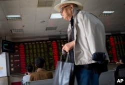 A man leaves as stock investors monitor the stock prices at a brokerage house in Beijing, China, Wednesday, July 8, 2015.