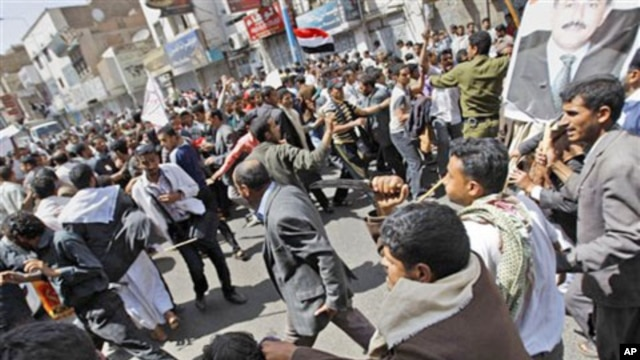 Supporters of the Yemeni government, right, reach to scuffle with anti-government demonstrators celebrating the resignation of Egyptian leader Hosni Mubarak and demanding the ouster of their own president, in Sana'a, Yemen, February 12, 2011