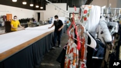 Workers at F.A.B.R.I.C., a non-profit organization, fold a large roll of fabric to make personal protective equipment after converting the fashion design warehouse to make gowns for area Dignity Health employees due to the coronavirus, April 13, 2020.