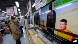 A man watches a television broadcasting a news about detained two Japanese, at an electronics store in Tokyo, Jan. 20, 2015.