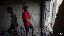포격으로 부서진 건물 안에 서있는 지역 주민