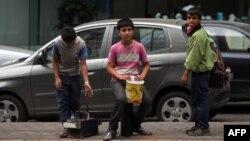 Các bé trai tị nạn người Syria xách dụng cụ đánh giày đi tìm khách hàng trên đường phố Beirut, Libăng.