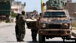 FILE - Kurdish fighters from the People's Protection Units (YPG) stand near a military vehilce in Qamishli city, Syria, April 22, 2016. U.S. officials prefer to view Syria's Democratic Union Party (PYD) and its YPG military wing as separate from the PKK.