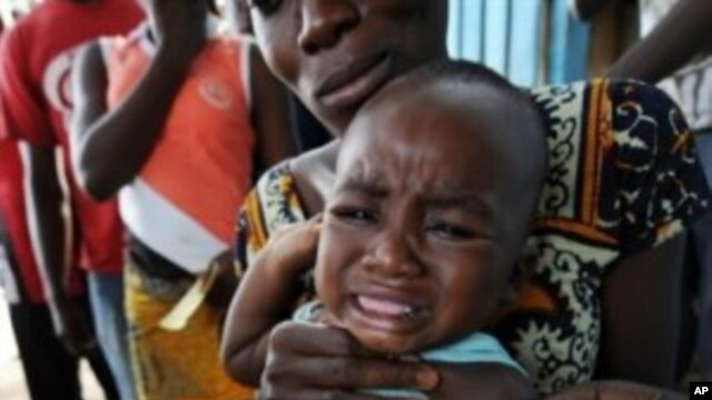 A health worker administers a yellow fever vaccine to a baby on a roadside in Koumassi, a poor area of Abidjan, after a case of yellow fever was discovered (File)