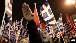 FILE - A supporter of Greece's extreme right Golden Dawn party gives a Nazi-style salute during a rally in Athens. The United States was one of three countries to vote against a U.N. resolution condemning the glorification of Nazism.