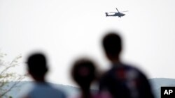 Migrants watch a helicopter of Greek army during exercises near the makeshift camp at the northern Greek border point of Idomeni, Greece, April 14, 2016.