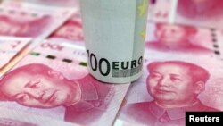 A 100-Euro banknote and Chinese 100-yuan banknotes are seen in this picture illustration, in Beijing, China, Jan. 21, 2016.