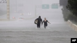 Two people walk down a flooded section of Interstate 610 in floodwaters from Tropical Storm Harvey, Aug. 27, 2017, in Houston, Texas.